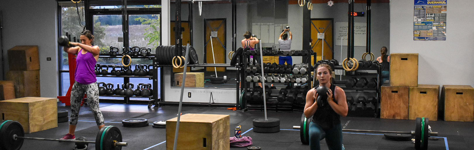 Two female members work out with kettlebells at CrossFit Alaska.