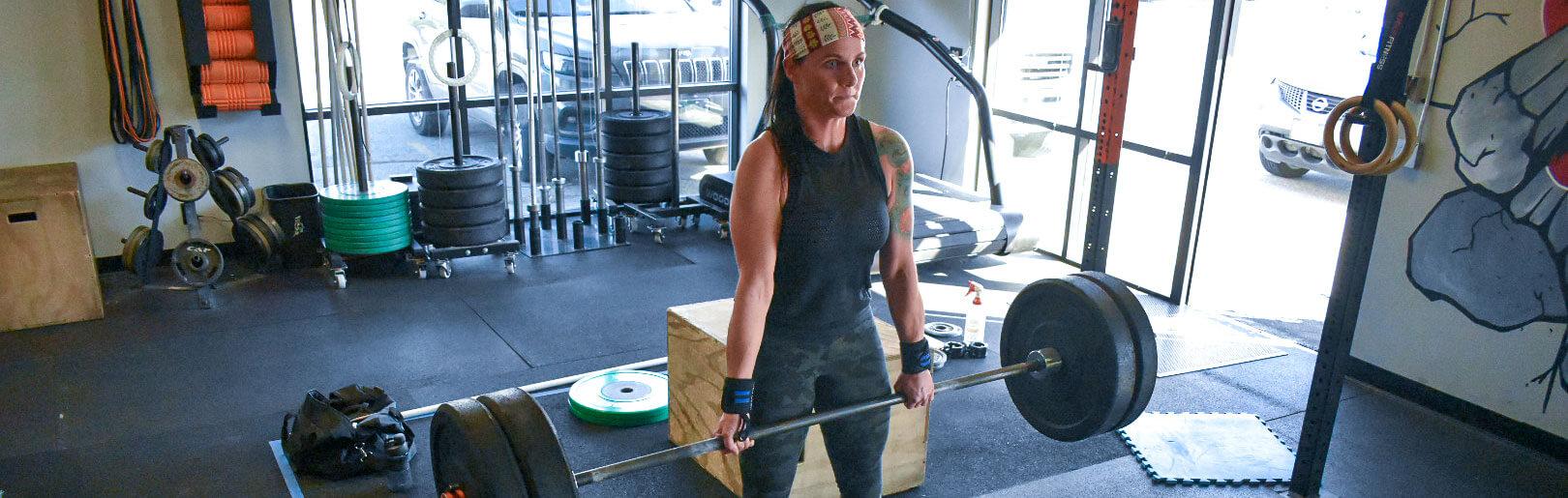 A female member deadlifts at CrossFit Alaska.