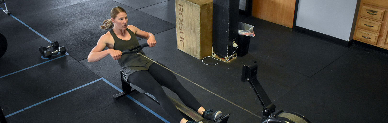 Female member rows on Concept 2 machine at CrossFit Alaska.