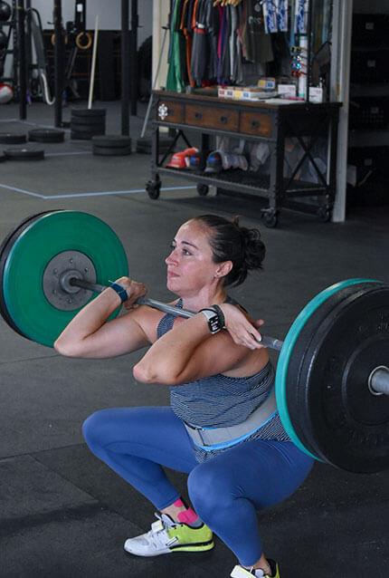 Female member power cleans at CrossFit Alaska.